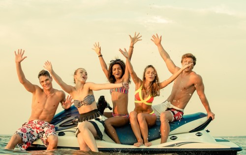 Group of happy multi ethnic friends sitting on a jet ski